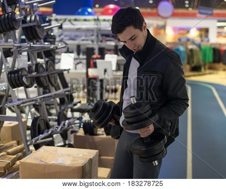 portrait of young male customer choosing dumbbells at supermarket store. He is holding dumbbells