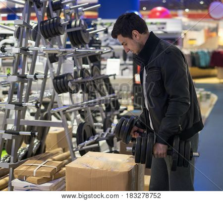 portrait of young male customer choosing dumbbells at supermarket store. He is putting dumbbells in box.
