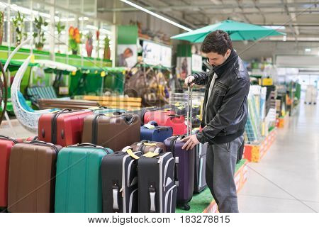 male customer choosing travel suitcase in the supermarket. He is holding handle