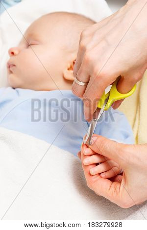 Mother Cutting Fingernails Of Newborn Baby, Body Care Concept