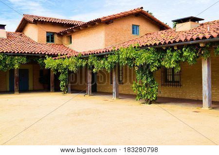 Historic Spanish style Hacienda Villa with hanging grapevines taken from its courtyard