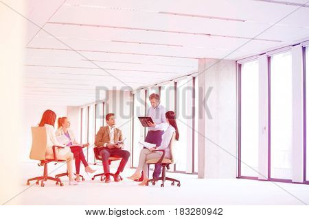Mature businessman having discussion with team on chair in new office