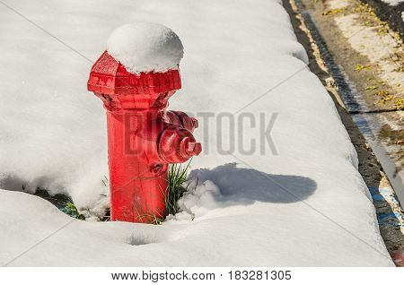 Snow-topped red fire hydrant after a heavy wet spring snowfall