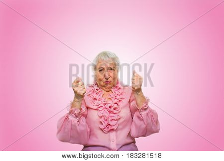 Elderly woman in suspense and determination on rose studio background. Concept of force