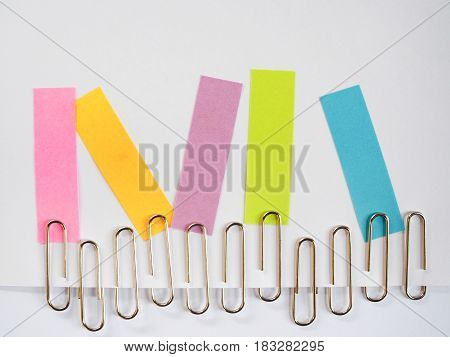 Silver Paper Clips And Colorful Sticky Notes On A White Background With Free Text Space.