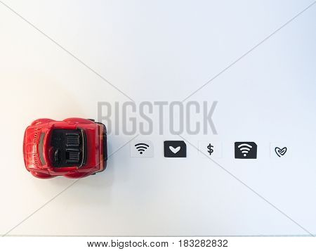 Small paper simulated as a SIM card and a red toy car on white background. Dollar wifi and heart symbol on paper sim cards