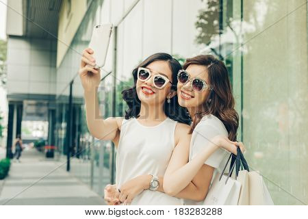 Beautiful asian girls with shopping bags taking selfie photo at the mall