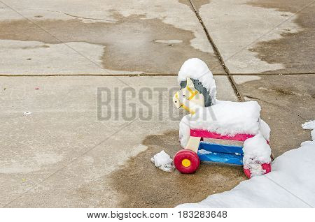 Plastic toy horse left outside and covered with snow
