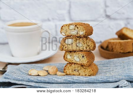 Close up of homemade biscotti cantuccini or cantucci Italian almond sweets biscuits (cookies) served with cup of coffee on wooden background.