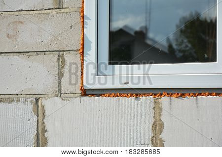 Windows installation and insulation in new house construction building.