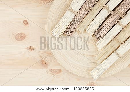 Assortment bundles of raw asian noodles on beige wooden dish on wood board top view. Decorative border with copy space.