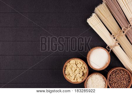 Assortment of bundles raw noodles with ingredient in wooden bowls on black striped mat background with copy space top view.