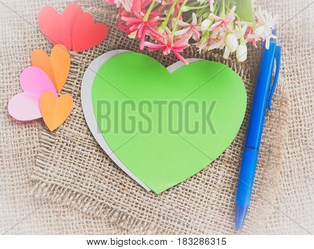 Poster mock up template with flower bouquet color paper in the shape of heart and blue pen on brown sack background