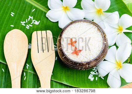 rice in coconut shell on banana leaf