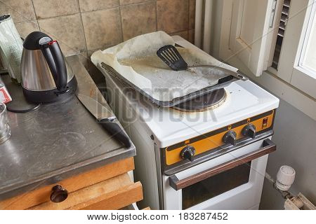 Part of a dirty, messy kitchen with stove
