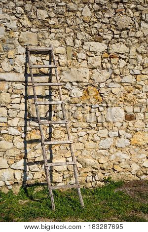 A wooden staircase standing on the grass and leaning against a wall of stones