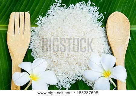 rice pile with wooden spoon on banana leaf
