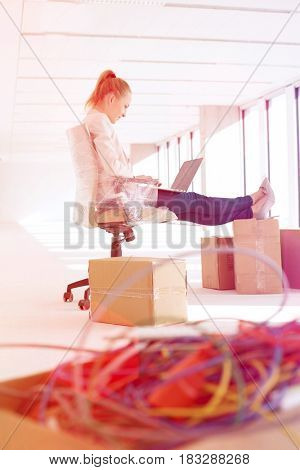 Side view of young businesswoman using laptop with feet up on cardboard box in office