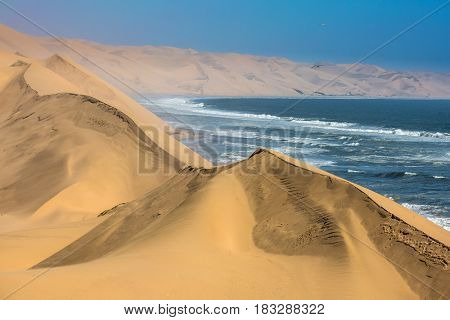 The concept of extreme and exotic tourism. Ocean surf with foamy waves. Gorgeous jeep - safari through the huge sand dunes. Atlantic coast of Walvis Bay, Namibia, south of Africa