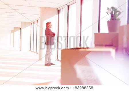 Side view of mature businessman looking through window in new office