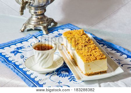 Professional bakery. Gorgeous white cheesecake, sprinkled with sweet crumbs. The background is a samovar and a thin porcelain cup with hot tea, on a blue patterned kitchen towel