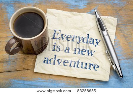 Everyday is a new adventure - motivational text on a napkin with a cup of coffee