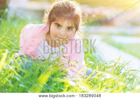 Portrait of a cute little girl having fun outdoors, adorable child  playing on fresh green grass field in bright sunny day, happy and carefree childhood