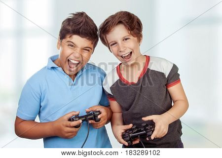 Best friends playing at home, crazy emotion of video games, two excited teen boys enjoying competition, laughing and screaming