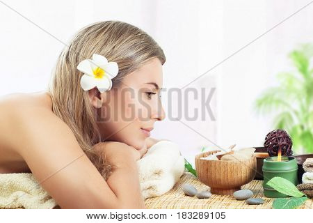Pretty woman at spa salon, profile of a nice female lying down on massage table, enjoying beauty procedure at the luxury spa resort