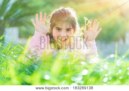 Pretty child playing outdoors, cute little girl raised up hands and laughing, having fun on the fresh green grass field in bright sun light, enjoying nice spring day