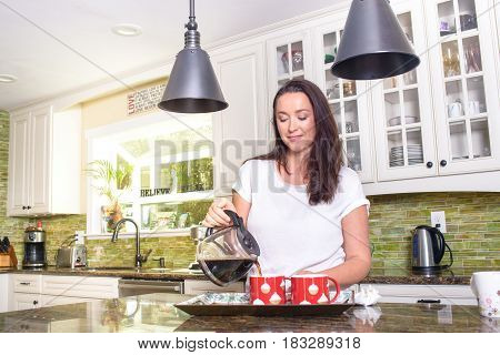 Attractive positive woman pouring homemade coffee in two cups in cozy modern sunny kitchen, smiling happily.