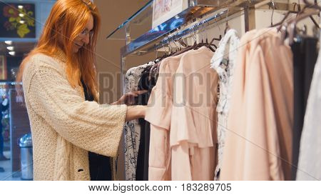 Attractive girl in a fashion dress store chose a clothe - shopping concept, close up