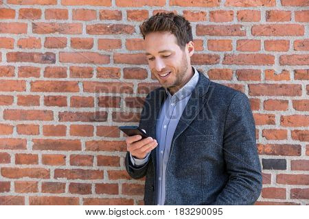 Young casual business man using smartphone in urban city background relaxing on brick wall texting sms on phone app living a modern lifestyle. Happy businessman playing mobile games.