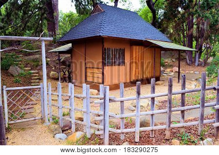 Japanese Teahouse surrounded by a rustic wooden fence and forest taken in a meditation garden