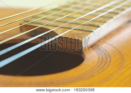 Old wooden string guitar closeup. Vintage acoustic music background. Musical classical instrument.