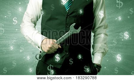 Handsome businessman holding tool with dollar symbols around and with green background