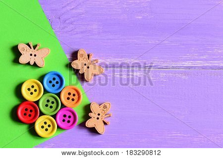 Colourful wooden round buttons laid out in the shape of a flower on a green paper sheet, wooden butterfly buttons. Wooden background with copy space for text. Fun summer card. Closeup. Top view