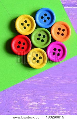 Colorful wooden round buttons laid out in the shape of a flower on a green paper sheet. Wooden background with copy space for text. Bright summer background. Closeup. Top view. Vertical photo