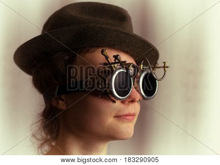 Portrait of attractive steampunk girl wearing goggles and hat on light background