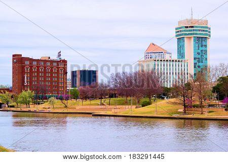 March 20, 2017 in Wichita, KS:  Downtown skyline beside the Arkansas River where people can walk on a pedestrian walkway beside the river while viewing the skyline taken in Wichita, KS