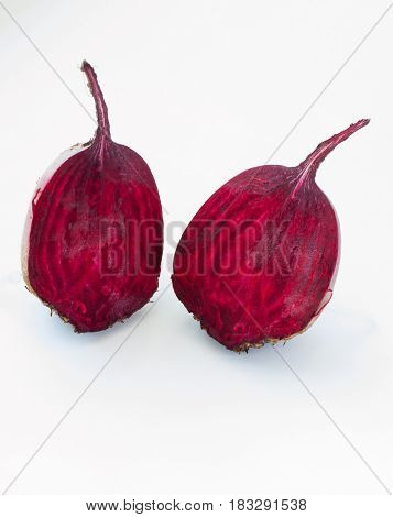 Cut into two parts red beet on white background