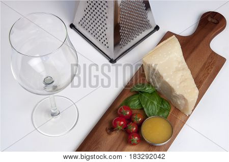 Parmesan cheese, still life italian food. Still life with parmesan cheese, grater, wineglass, honey, cherry tomatoes and basil on a wooden chopping board.