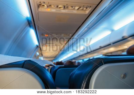 Interior of airplane with passengers on seats shallow DOF