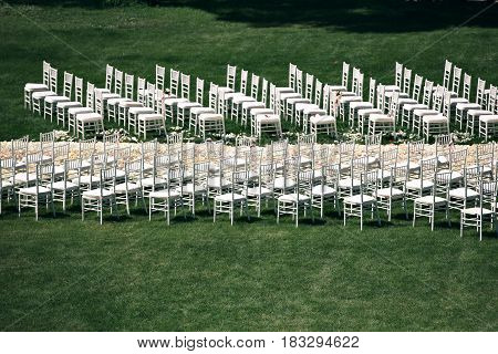 Beautiful wedding ceremony design decoration elements with fresh flowers composition, floral design, petals roses and chairs