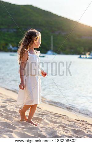Adorable little girl at tropical beach enjoying sunset
