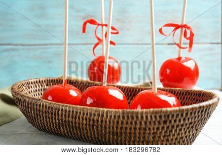 Delicious holiday apples in wicker basket against wooden background