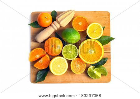 Wooden board with delicious citrus fruits and hand juicer on white background