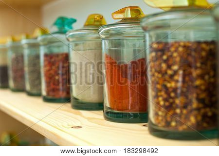 Close up picture of dried spices in glass jars on a wooden shelf in the kitchen