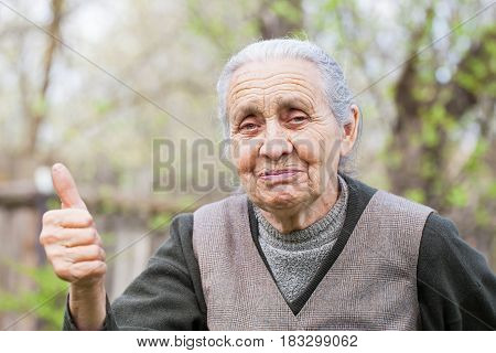 Picture of a happy senior woman showing thumb up outdoor