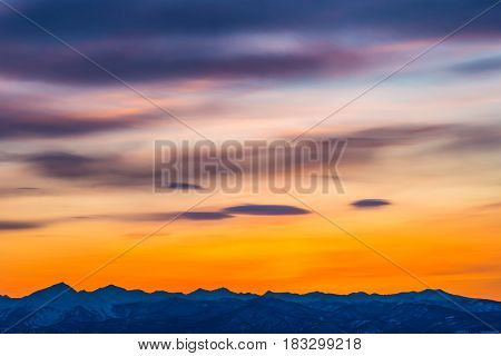 Orange sunset with purple clouds above mountains